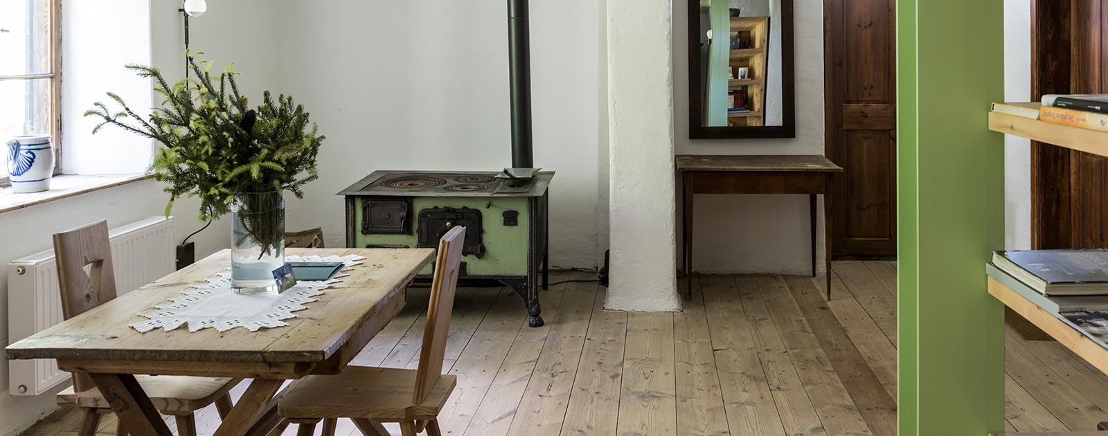 the dining table and an antique wood-burning oven in a room of the Settari house of the Briol hotel in Barbiano